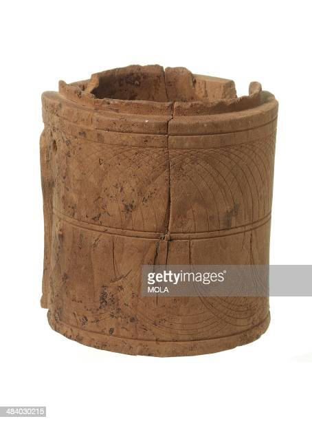 Almost complete latheturned wooden cylindrical box the shape now distorted with compassinscribed decoration 2nd century AD from the 1976/1989...