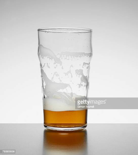 Almost empty glass of beer indoors