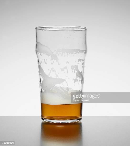 Almost empty glass of beer indoors