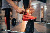Cropped shot of a man tying his shoelaces at the gym