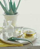 Aloe, tea and oils on a platter.