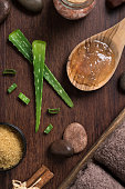 Stem of aloe vera plant on wooden background with himalayan salt and stones. Top view of aloevera gel on wooden spoon with beauty spa setting on table. High angle view of beauty treatment at sap salon