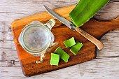 Healthy Aloe vera juice in a mason jar glass. Top view scene on a wooden paddle board.