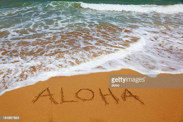 Aloha written in sand on the beach with tide coming in