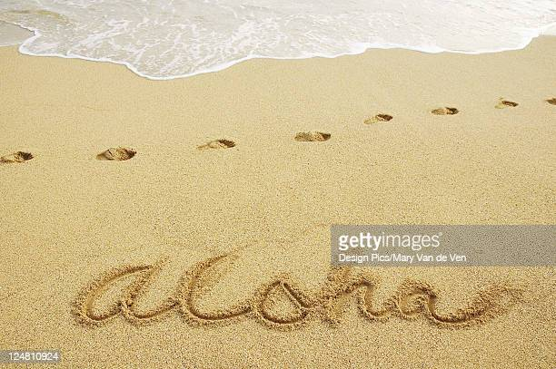 Aloha written in sand with footprints and wave wash.
