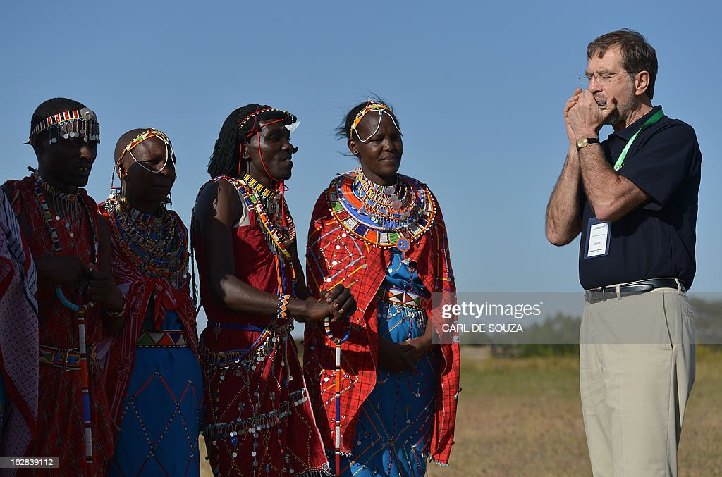 Alojz Peterle, head of the European Union Election Observation Mission (EU EOM) in Kenya plays the harmonica for Maasai people in Kiserian, outside Nairobi on February 28, 2013. Kenya is preparing for national elections on March 4, 2013 and the European Union has sent observers to report on the process and outcome. AFP PHOTO/Carl de Souza