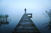 Depressed man standing alone on a jetty on a foggy autumn day.