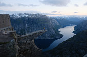 Alone tourist on Trolltunga rock - most spectacular and famous scenic cliff in Norway