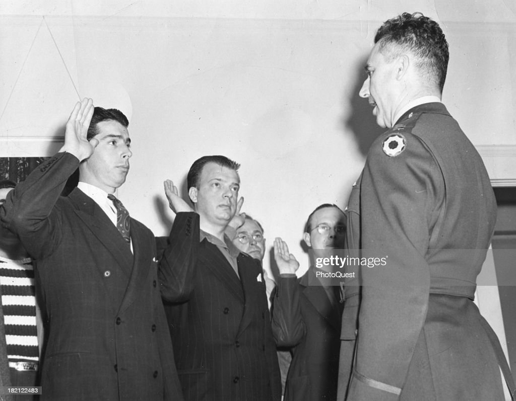 Along with several unidentified inductees, American baseball player Joe Dimaggio (1914 - 1999) (left) is sworn into the US Army Captain M.A. Branson at an unspecified induction center on the West Coast, February 1943.