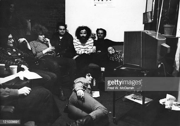 Along with unidentified others American political and social activists Abbie Hoffman and Jerry Rubin watch televison coverage of the Black Panther...