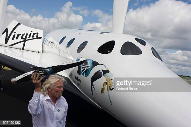 Alongside his SpaceShipTwo vehicle Richard Branson holds model of satellite LauncherOne after Virgin Galactic space tourism presentation at the 2012...