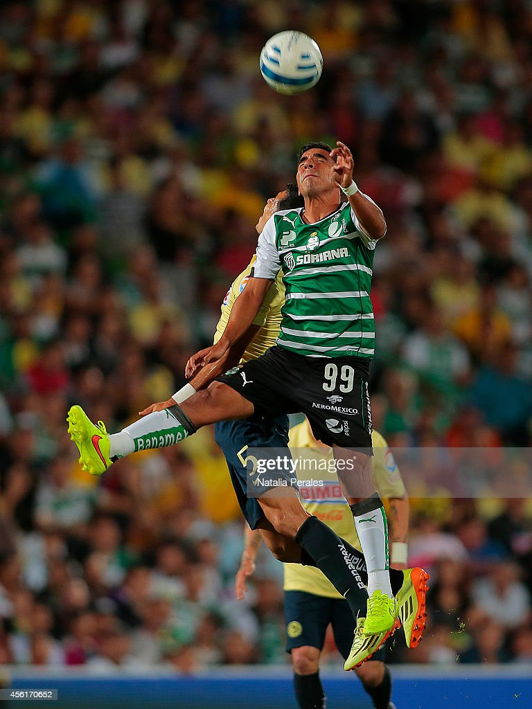 <a gi-track='captionPersonalityLinkClicked' href=/galleries/search?phrase=Alonso+Escoboza&family=editorial&specificpeople=8327045 ng-click='$event.stopPropagation()'>Alonso Escoboza</a> of Santos jumps for the ball over the mark of Jesus Molina of America during a match between Santos Laguna and America as part of 10th round Apertura 2014 Liga MX at Corona Stadium on September 26, 2014 in Torreon, Mexico.