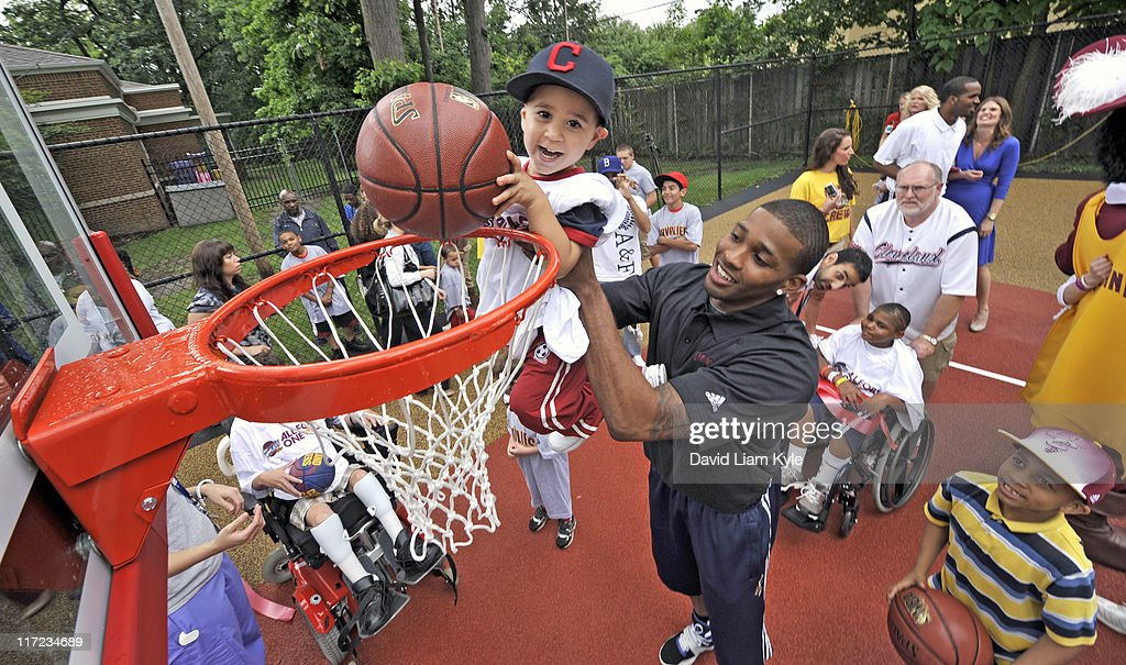 <a gi-track='captionPersonalityLinkClicked' href=/galleries/search?phrase=Alonzo+Gee&family=editorial&specificpeople=801443 ng-click='$event.stopPropagation()'>Alonzo Gee</a> of the Cleveland Cavaliers assists a young boy in dunking the ball at the newly remodeled basketball courts at the Cleveland Clinic Children's Hospital for Rehabilitation on June 24, 2011 in Cleveland, Ohio.