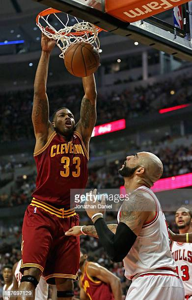 Alonzo Gee of the Cleveland Cavaliers dunks the ball over Carlos Boozer of the Chicago Bulls at the United Center on November 11 2013 in Chicago...
