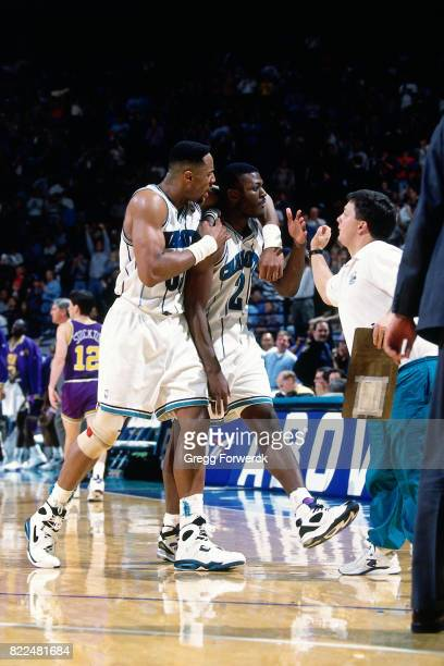 Alonzo Mourning of the Charlotte Hornets walks with teammate Larry Johnson during a game against the Utah Jazz at the Charlotte Coliseum in Charlotte...