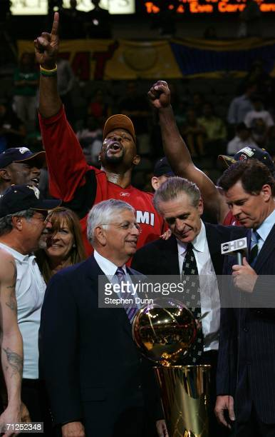 Alonzo Mourning of the Miami Heat stands in the back and cheers as head coach Pat Riley is given the Larry O'Brien Trophy after the Heat won the 2006...