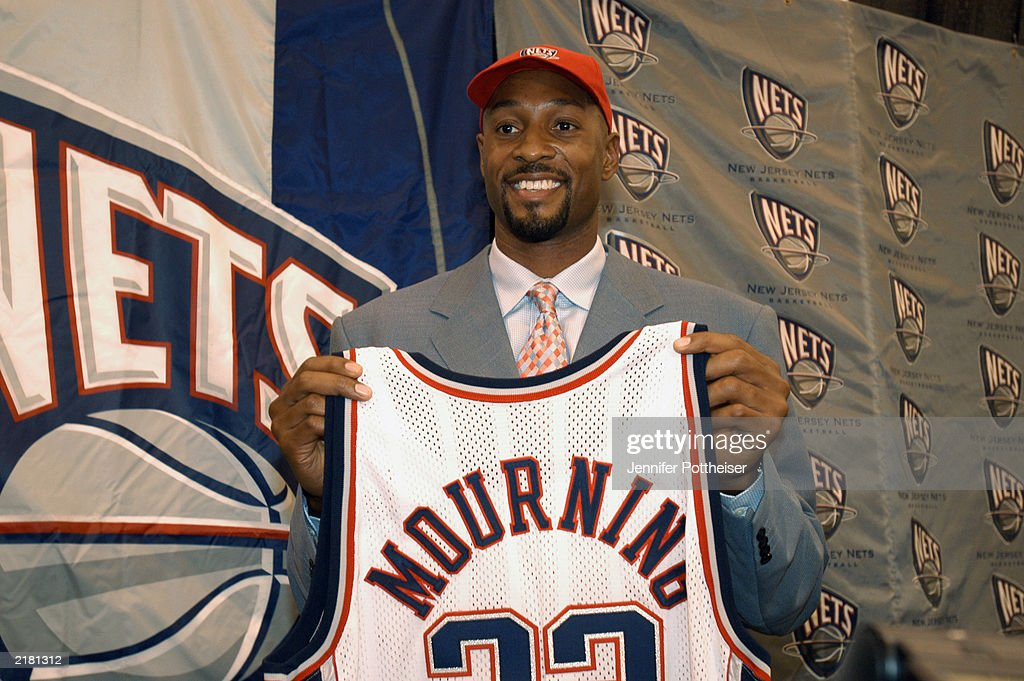 ... Alonzo Mourning 33 of the New Jersey Nets holds up his new uniform  during a ... 25e6203a9