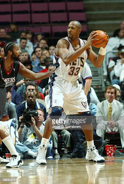 Alonzo Mourning of the New Jersey Nets looks to pass the ball against the Philadelphia 76ers at Continental Airtlines Arena on October 14 2003 in...