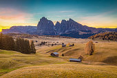 Beautiful view of traditional wooden mountain chalets on scenic Alpe di Siusi with famous Langkofel mountain peaks in the background in golden morning light at sunrise, Dolomites, South Tyrol, Italy