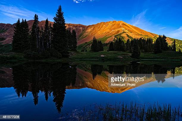 Alpenglow on Mountain Peaks Reflecting in Lake