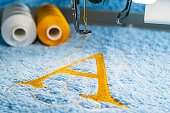 Yellow A alphabet logo design and two color threads on blue towel in hoop of embroidery machine, close up picture