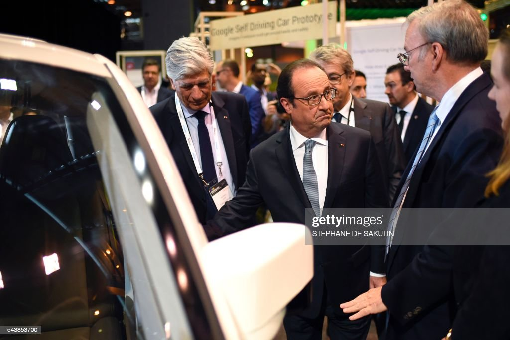 Google CEO Eric Schmidt (2nd L) gestures as he talks to French President Francois Hollande (2nd R), next to Publicis Group Directory Board Chairman Maurice Levy (L) and French Minister of State for the Digital Sector Axelle Lemaire (R) in front of the Google's self driving car project during a visit to the Viva technology event in Paris on June 30, 2016. / AFP / STEPHANE