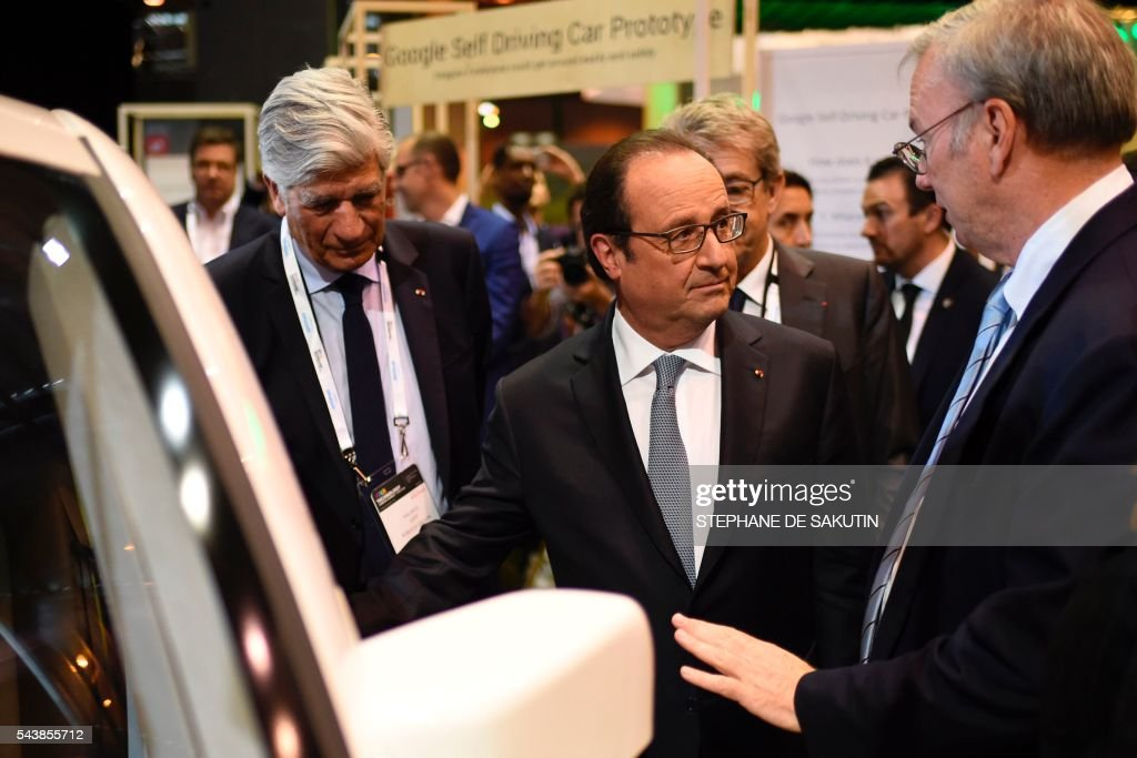 Google CEO Eric Schmidt (2nd L) gestures as he talks to French President Francois Hollande (2nd R), next to Publicis Group Directory Board Chairman Maurice Levy (L) in front of the Google's self driving car project during a visit to the Viva technology event in Paris on June 30, 2016. / AFP / STEPHANE
