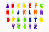 Alphabet written in colorful plastic magnetic letters on a white background.