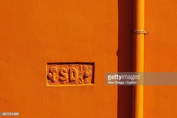 Alphabets Carved By Pipe On Orange Wall