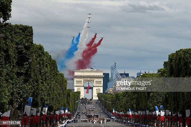 TOPSHOT Alphajet aircrafts from the French elite acrobatic flying team Patrouille de France release smoke in the colours of the French national flag...