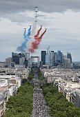 Alphajet aircrafts from the French elite acrobatic flying team Patrouille de France release smoke in the colours of the French national flag above...