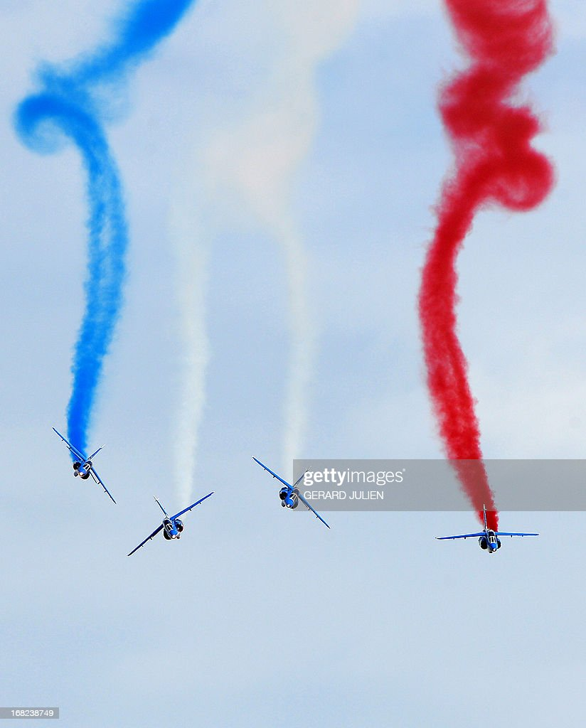 Alphajets from the French elite acrobatic flying team 'Patrouille de France' (PAF) perform aerobatics and release trails of blue, white and red smokes representing the French national flag's colors, as they fly over the 701 Air Base of Salon-de-Provence, southern France, on May 7, 2013. The Patrouille de France will celebrate its 60th anniversary on May 25 and 26. AFP PHOTO / GERARD JULIEN