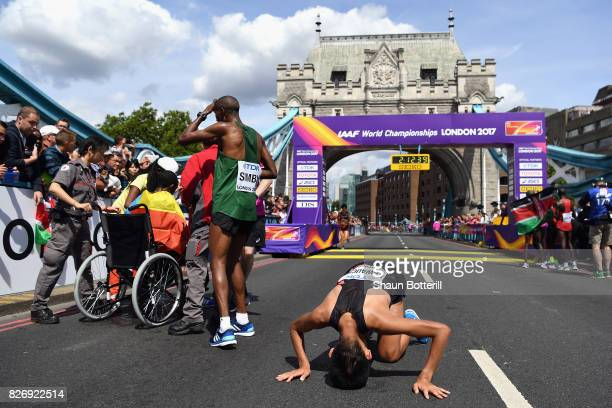 Alphonce Felix Simbu of Tanzania and Yuki Kawauchi of Japan react after crossing the finishline in the Men's Marathon during day three of the 16th...