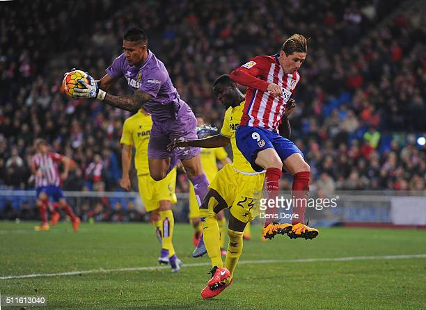 Alphonse Areola of Villarreal CF saves from a challenge by Fernando Torres of Club Atletico de Madrid during the La Liga match between Club Atletico...