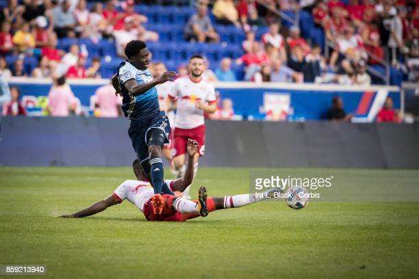 Alphonso Davies of the Vancouver Whitecaps FC is stopped by Kemar Lawrence of New York Red Bulls during the MLS match between New York Red Bulls and...