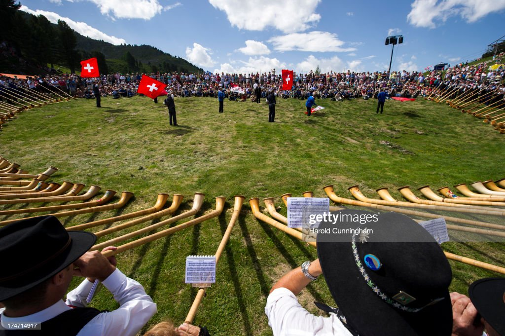 Alphorn players and flag trowers perform on July 28, 2013 in Nendaz, Switzerland. About 150 alphorn blowers performed together on the last day of the international Alphorn Festival of Nendaz. The Swiss folkloric wooden wind instrument was used in most mountainous regions of Europe by mountain dwellers as signal instruments.