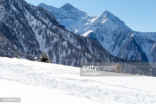 Alpine landscape with mountains, trees and snow : Stock Photo