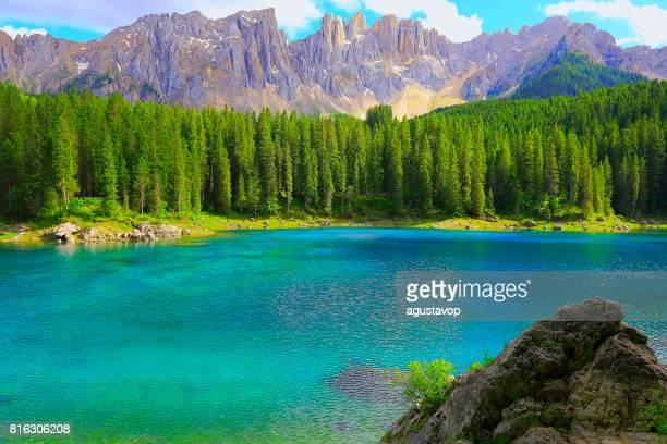 Alpine Turquoise Carezza lake (Lago di Carezza or Karersee), idyllic landscape near majestic Latemar Massif alps valley, dramatic Italian South Tirol Dolomites Snowcapped mountain range panorama, Italy