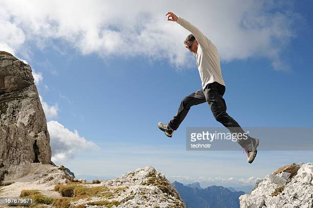 Alpinist jumping over the precipice