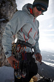 Alpinist on mountain top, checking equipment, Zugspitze, Bavaria, Germany