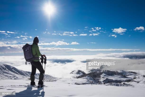 Alpinist sulla cima della montagna innevata