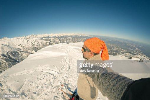 Alpinista tomando autofoto en nevosa, ojo de pez lente : Foto de stock