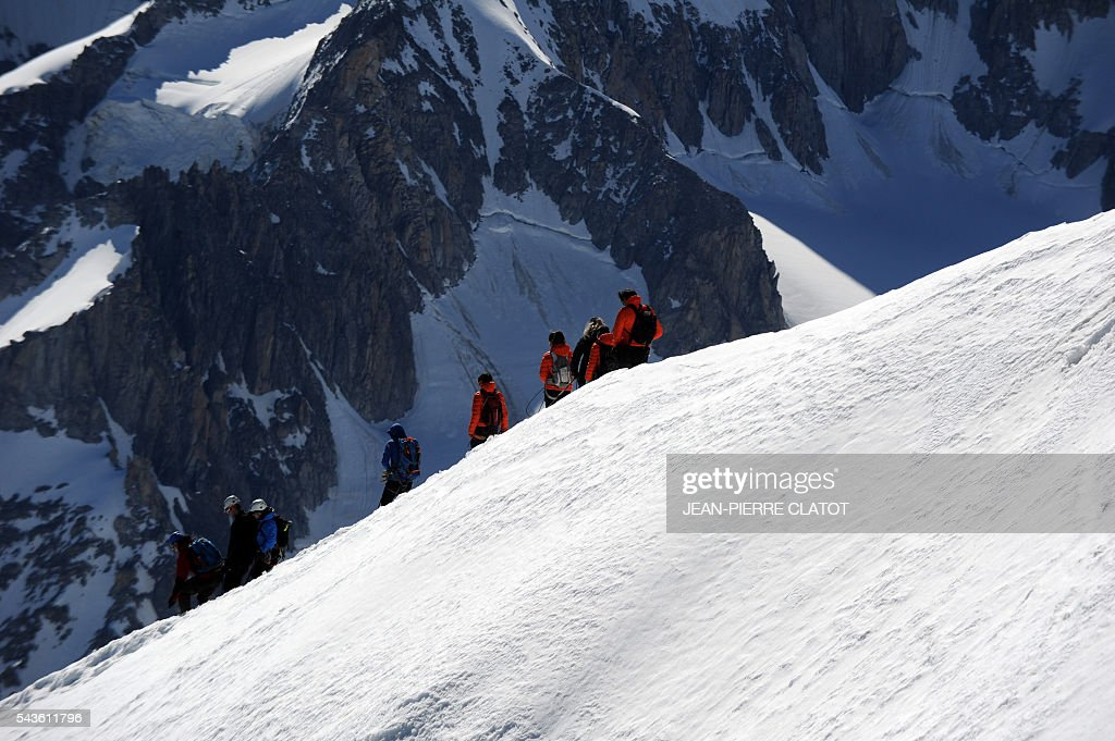 Alpinists walk on the Mont-Blanc Massif above the vallee blanche in the French Alps on June 29, 2016. / AFP / JEAN
