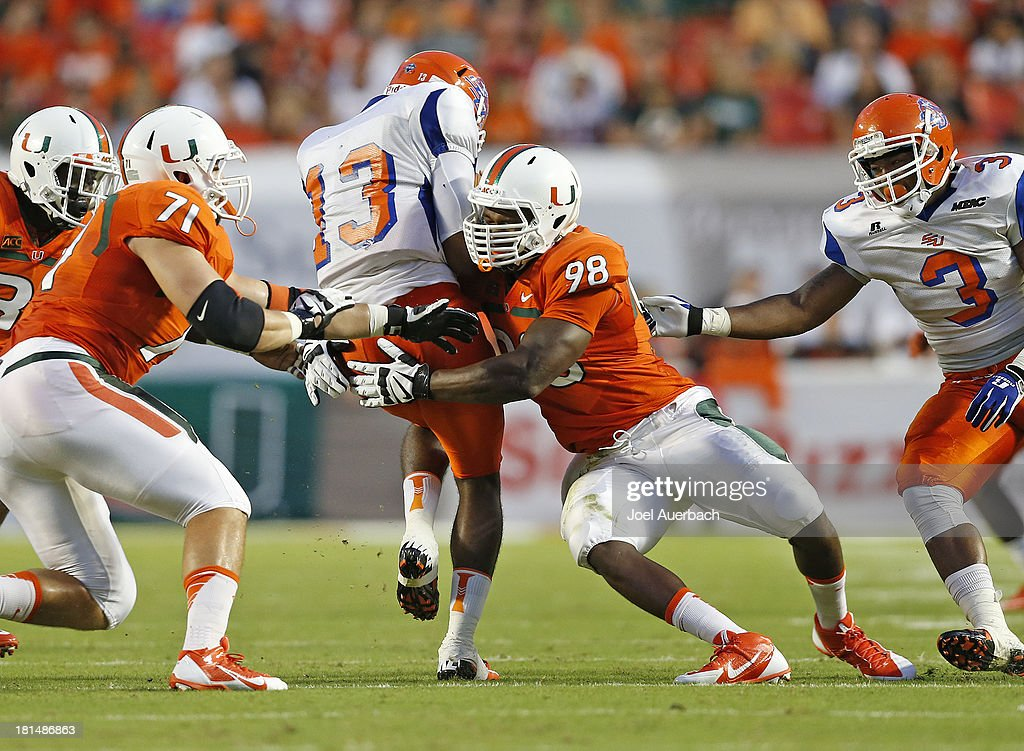Al-Quadin Muhammad #98 of the Miami Hurricanes sacks Antonio Bostick #13 of the Savannah State Tigers on September 21, 2013 at Sun Life Stadium in Miami Gardens, Florida.