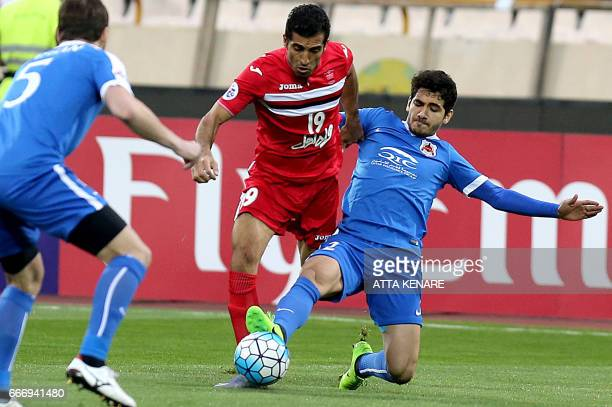 AlRayyan's Mohamed Alaaeldin vies for the ball against Persepolis' Vahid Amiri during the Asian Champions League football match between Qatar's...