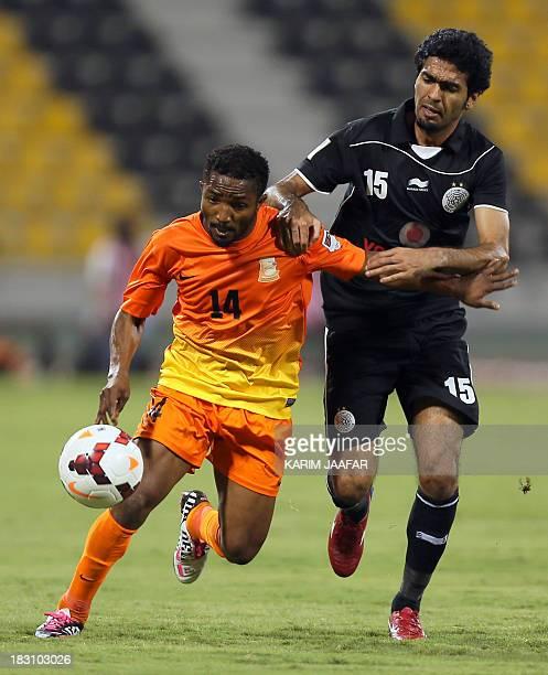 AlSadd's Qatari midfielder Talal AlBloushi tries to take the ball away from Umm Salal's Ivorian forward Bakari Kone during their Qatar Stars League...