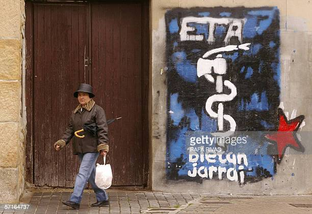 A woman walks past the logo of the proindependence armed Basque group ETA 23 March 2006 in the northern Spanish village of Alsasua Navarra province...