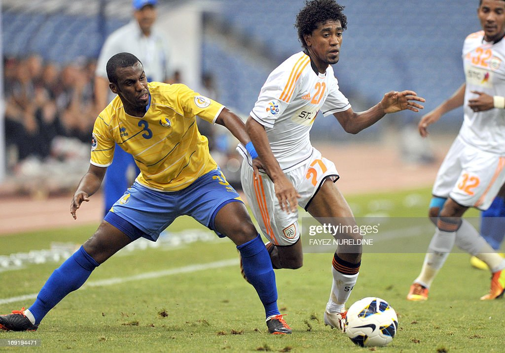 Al-Shabab club player Saeed Al Dosari (C) dribbles past Al Gharafa Meshal Mubarak during their AFC Champions League football match at King Fahad International stadium in Riyadh, on May 21, 2013.