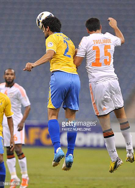AlShabab club player Sebastian Tagliabue fights for the ball with Al Gharafa Ibrahim Al Ghanim during their AFC Champions League football match at...
