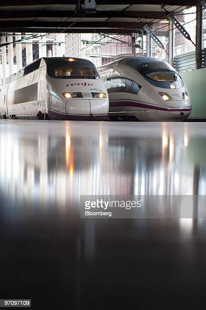 Alstom left and Siemens locomotives operated by Renfe for their highspeed AVE service sit at the platform at Atocha station in Madrid Spain on...